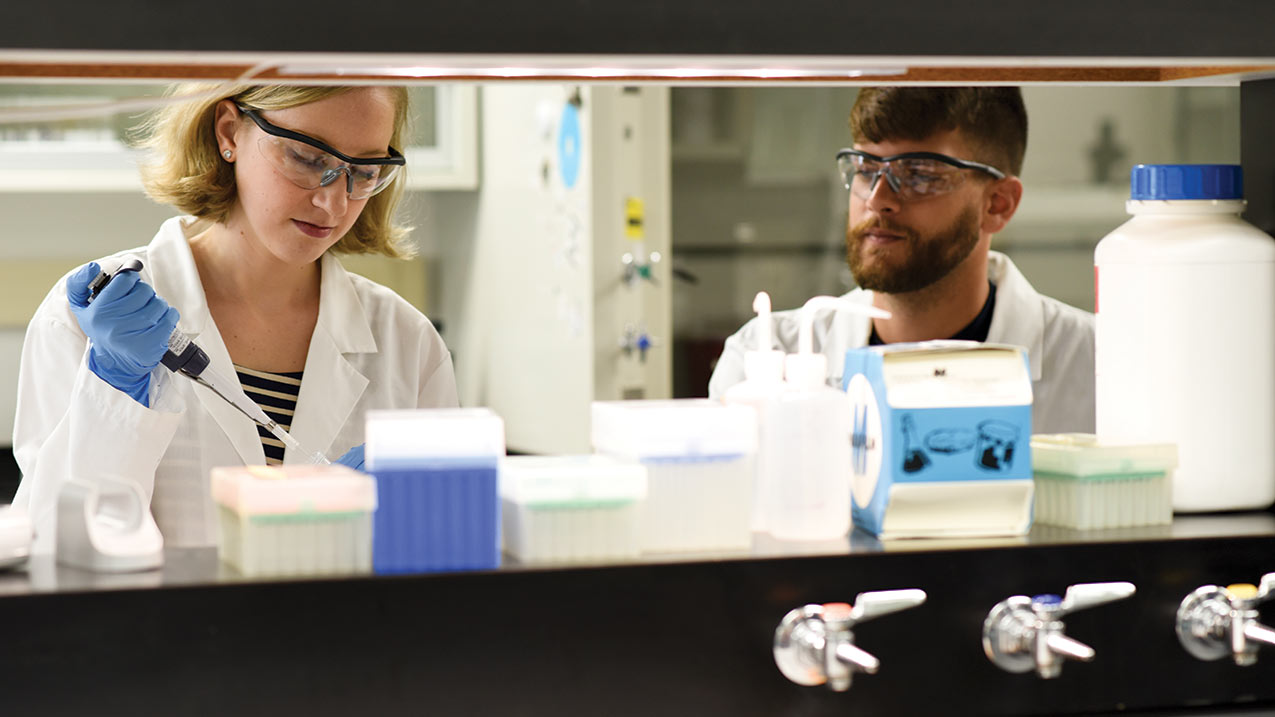 Student working in a lab with a lab tech.