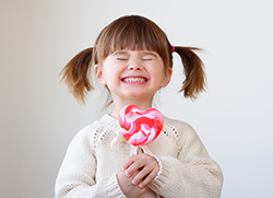 Smiling child holding a lollipop