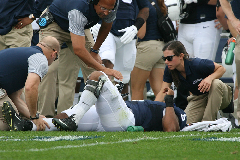 Athletic Training student tends to injured football player