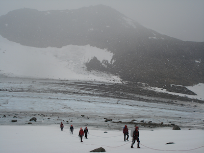 A group of people walking at the base of a mountain in snowy conditions.