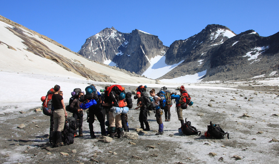 A group of people standing at the base of a mountain.