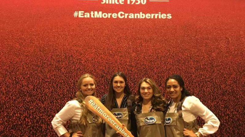 SNA members Valerie Snell, Mackenzie Lombardi, Madison Galascio and Paris Winston in front of a large Ocean Spray poster.