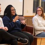 Three students sitting with one student speaking on a microphone.