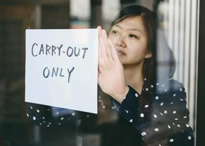 "Woman hanging ""carry-out online"" sign in restaurant window"