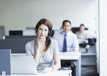 Woman in office at desk wearing headset with coworkers at desks in the background