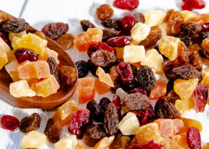 A variety of dried fruit mix spilled on a table