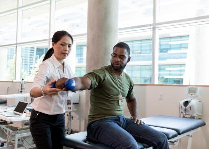 A female doctor helps a male veteran patient with physical therapy on his arm.