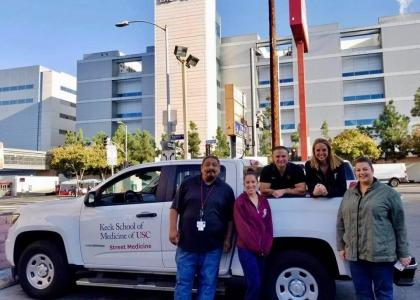 Brett Feldman and some of his team members stand by a white pickup truck in front of a hospital in LA
