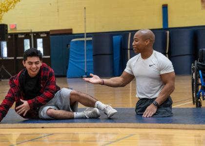Rohan Murphy presenting at high school gym with student