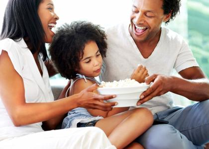 A family of three smiles as they enjoy a bowl of popcorn