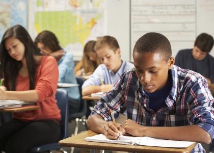 Students classroom writing in notebooks