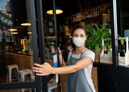 Woman in mask opening a restaurant for business