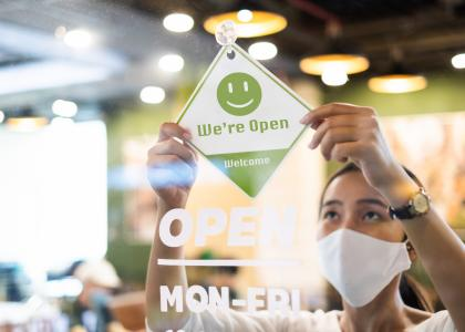 Woman in white mask hanging Open sign in restaurant window