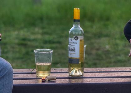 cup of wine next to wine bottle on bench