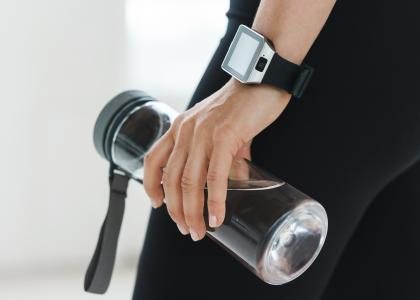 A hand wearing a Smartwatch and holding a water bottle