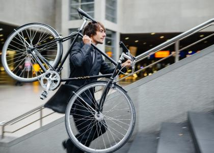 man in business suit carrying bike