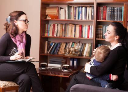 Woman talking to woman holding baby in office