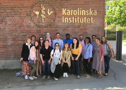 Students pose next to Karolinska Institute sign