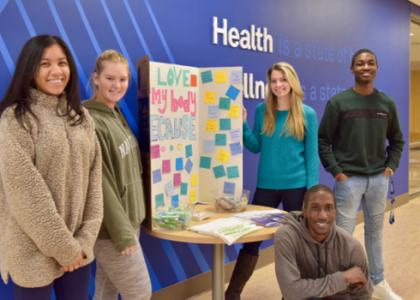 A diverse group of HealthWorks peer mentors pose during a community outreach event