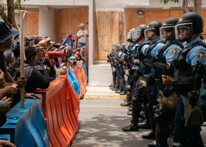 Protesters stand facing police officers in Puerto Rico