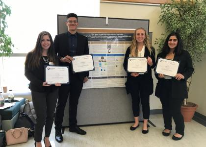 Four students posing in front of research poster