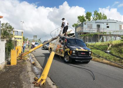People attempt to remove broken power poles that landed on top a food truck in Vega Alta, Puerto Rico after Hurricane Maria.