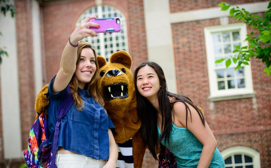 Students on campus with the Nittany Lion mascot.