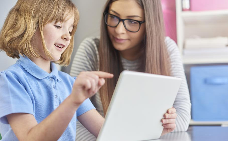 Adult working with a young girl on an iPad.