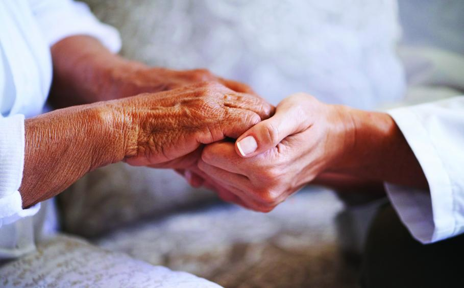 Two people holding hands, one young person and one elderly person.