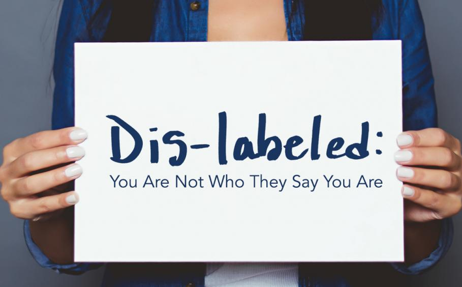 Woman holding a sign. Dis-labeled: You Are Not Who They Say You Are