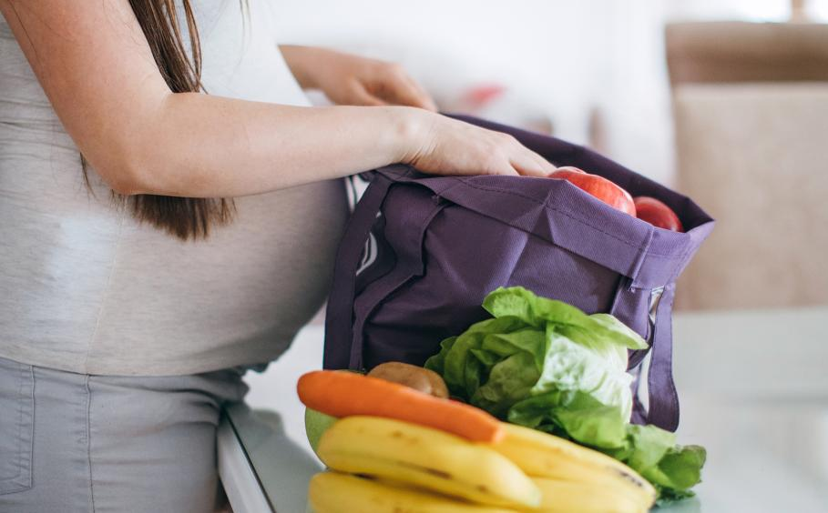 A pregnant woman unpacking fruits and vegetables.
