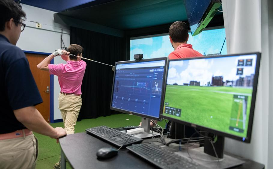 Two computers in the foreground and two instructors working with a golfer in the Golf Teaching and Research Center