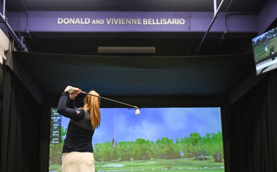 Female student at the top of her golf swing in the Donald and Vivienne Bellisario GTRC portal