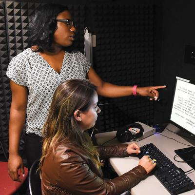 Students working in a computer in a sound proof booth.