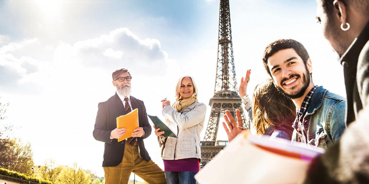 Students in front of the Eiffel Tower in discussion with their professor.