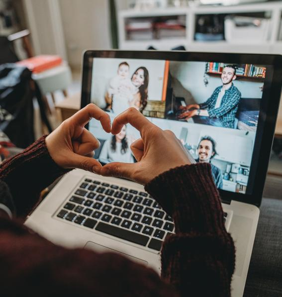 Person holding hands in the shape of a heart to others on a video call.